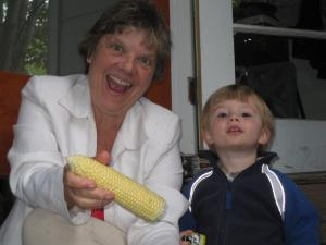 Gramma Mia and Sylvan pose while shucking corn on the back step
