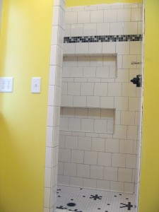 Looking into shower this morning. Note shelves, glass tiles for accent, and funky floor.