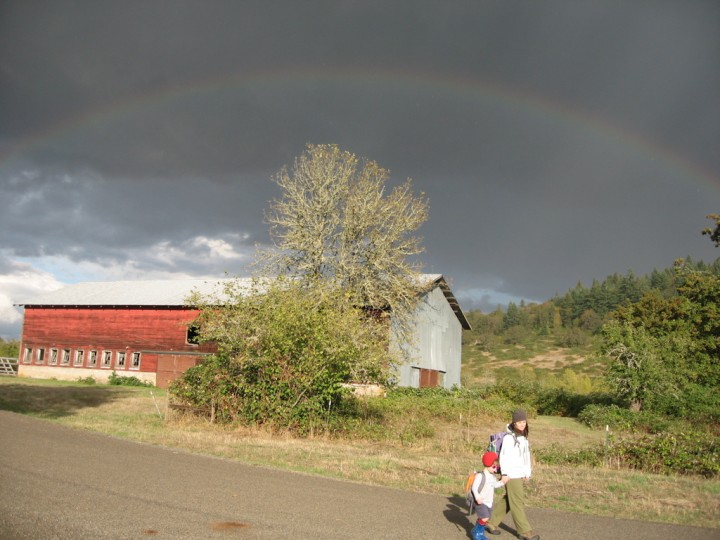 Julie and Sylvan walk in front of a rainbow and the Kienzle barn at Mt. Pisgah, 3 Oct 2009